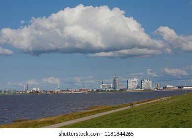Blexen, Germany - September 01, 2018: landscape with dike, small way, water and vivid blue sky with white clouds in front of the skyline of Bremerhaven, a man can be seen sitting on a bank far away