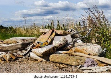 Blight of illegally dumped household rubbish left in a little used country lane. Environmental hazard, with furniture. mattresses and carpets. Fly tipped detritus. Oxfordshire.