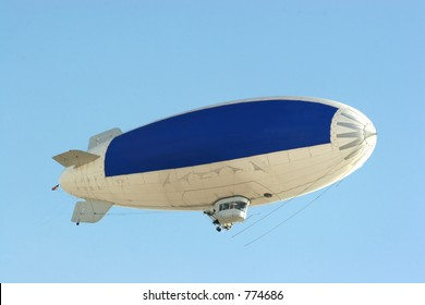 blimp flying in clear blue sky with blue copy space to advertise your message