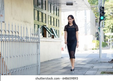 A blind asia woman walking on sidewalk with a cane.