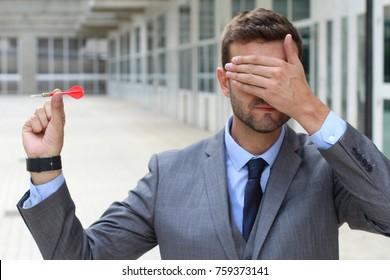 Blind businessman holding a dart