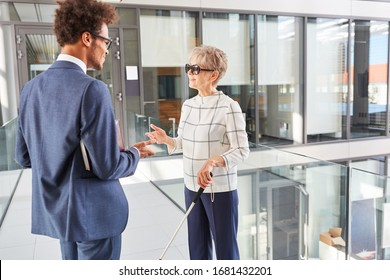 Blind businesswoman with long stick talking to African businessman