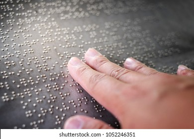 The blind fingers touching the Braille letters on the metal plate