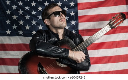 Blind guitar player on the background of the American flag in a leather jacket