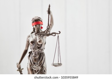 Blind Justitia figure with blindfold as law concept against wood background