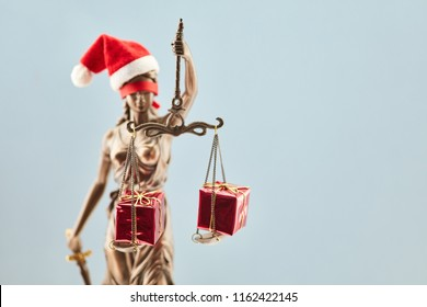 Blind Justitia as Santa with gifts for Christmas