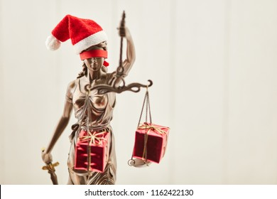Blind Justitia with Santa hat at Christmas with gifts on her Libra
