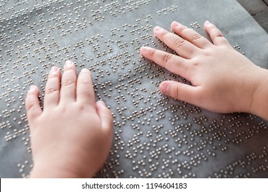 The blind kid's hand and fingers touching the Braille letters on the metal plate to understand an information