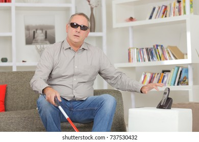 blind man at home reaching for the telephone