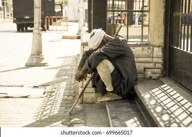 The blind man is a homeless man sitting on the floor.