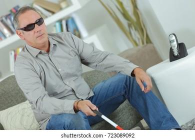 Blind man sat at home holding stick