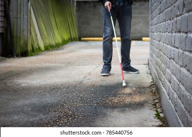 Blind Man Walking Near Wall inside an Alley with White Cane;  (Copy Space)