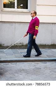 A blind man walks with a cane on a street