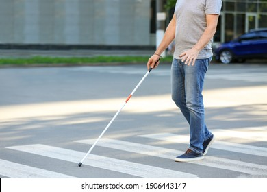 Blind mature man crossing road outdoors
