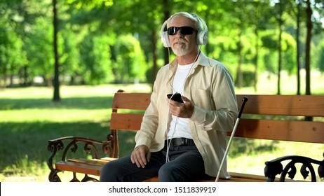 Blind old man wearing earphones listening audiobook, voice message in cellphone