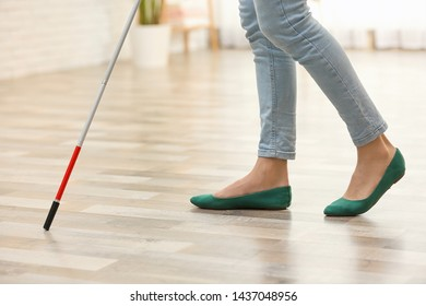 Blind person with long cane walking indoors, closeup