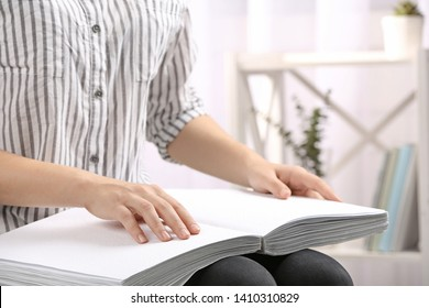 Blind person reading book written in Braille indoors, closeup