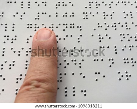 Blind person reads braille alphabet text. Close up finger touch to braille Code
