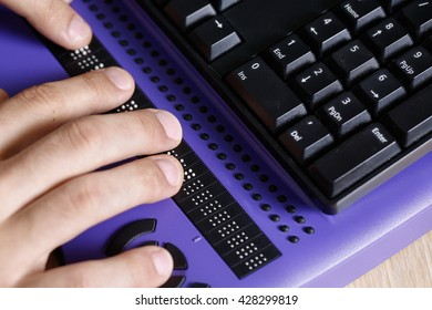 Blind person using computer with braille computer display and a computer keyboard. Blindness aid, visual impairment, independent life concept.