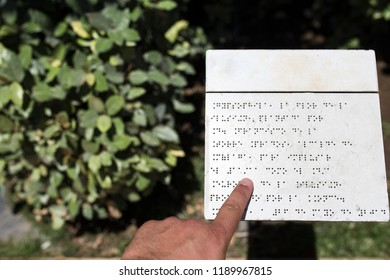 Blind reading text caption in braille language at garden. Accesible gardens concept