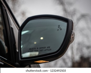 Blind Spot Monitoring system warning light/icon in side view mirror of a modern vehicle.