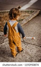 Blind or Visually Impaired Child/Kid/Toddler/Preschooler/Boy Walking Through Neighborhood with Long White Cane; At Sidewalk Corner; Back to Camera