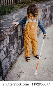 Blind or Visually Impaired Child/Kid/Toddler/Preschooler/Boy Walking Through Neighborhood with Long White Cane, Exploring Concert Wall Ledge