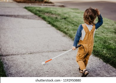 Blind or Visually Impaired Child/Kid/Toddler/Preschooler/Boy Walking Through Neighborhood with Long White Cane; Back to Camera (Copy Space)