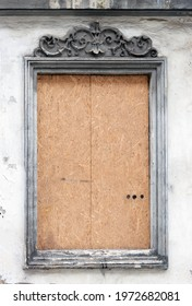 A blind window on the facade of an old tenement house. Window   boarded to secure.
