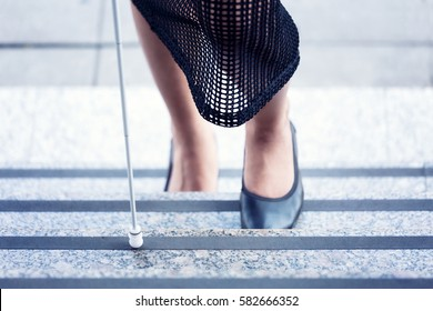 Blind woman going up the stairs with the white cane