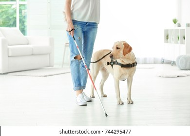 Blind woman with guide dog at home