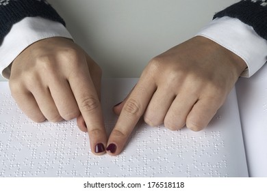 Blind woman reading text in braille language