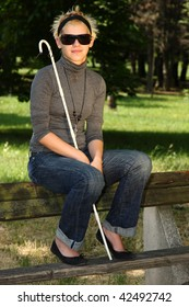 blind woman sitting on a bench in a park