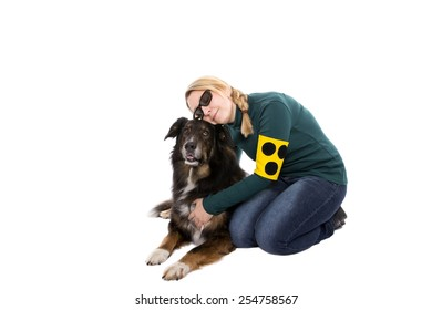 A blind woman is touching her guide dog and cuddles with him