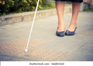 The blind woman is walking on the sidewalk, using a cane.