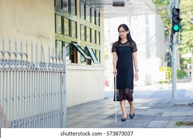 Blind Woman Walking On Sidewalk
