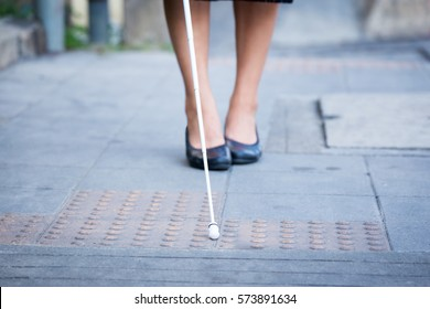 Blind woman is walking on the sidewalk, using a white cane.