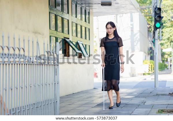 Blind Woman Walking On Sidewalk