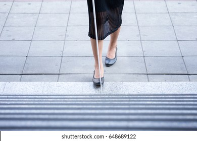 A blind woman walking up the stairs alone with a white cane