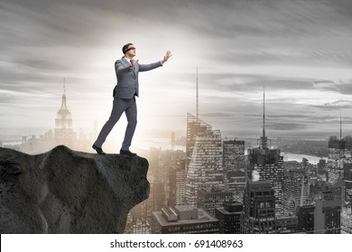 Blindfold businessman standing on tip of cliff