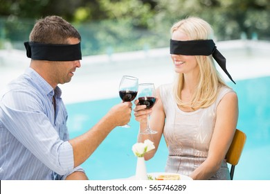 Blindfolded couple toasting red wine while sitting at poolside