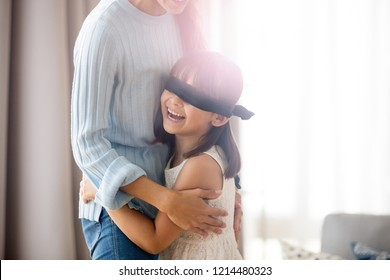 Blindfolded laughing little preschool daughter with covered eyes playing with mother hide and seek game standing embracing mommy caught her. Happy family spending free time on weekend have fun at home