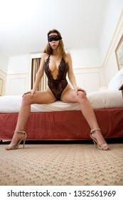 Blindfolded sexy woman wearing lingerie sitting on the bed