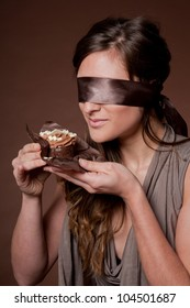Blindfolded woman holding cake