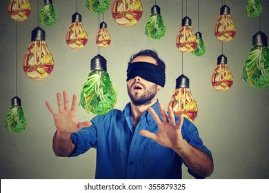 Blindfolded young man walking through light bulbs shaped as  junk food and green vegetables isolated on gray wall background. Diet choice right nutrition healthy lifestyle concept
