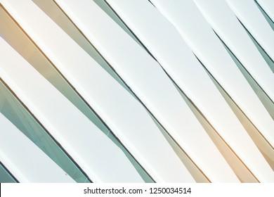 Die Jalousien auf dem Glas aus dem Metall. Fassade aus Glas und Metall. Streifen diagonale Linien der hellen Farbe. Modernes Design in der Architektur.