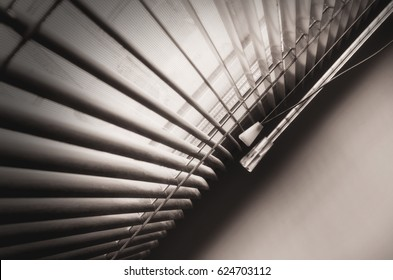 Blinds at a window. Monochrome image. Low contrast. Blackout at the edges. Indoors. Horizontal format. Photo.