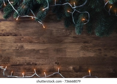 Blinking Christmas decorative light string with green pine leaves on wood table background, top view border design with copy space