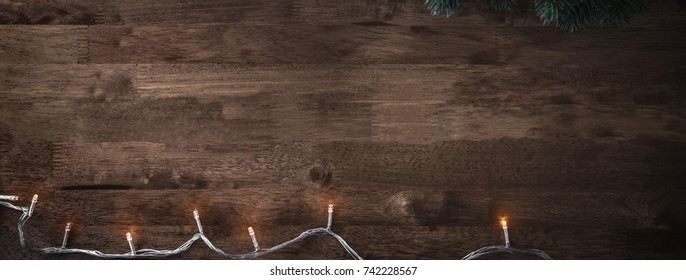 Blinking Christmas decorative light string with green pine leaves on wood table background, top view border design banner with copy space