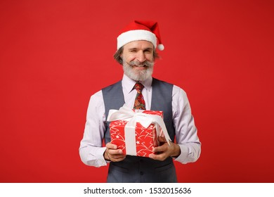 Blinking elderly gray-haired mustache bearded Santa man in Christmas hat, shirt vest tie isolated on red background. New Year 2020 celebration concept. Mock up copy space. Hold present box with gift.